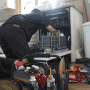Photo of an appliance repair technician repairing a dish washer.