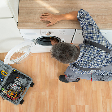 Photo of an appliance repair technician repairing a dryer.