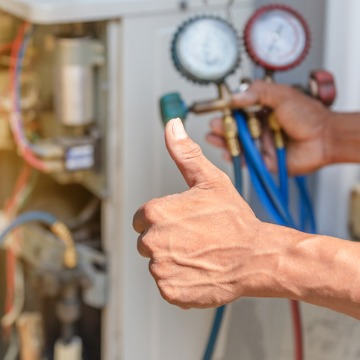 A repair technician giving a thumbs up after providing HVAC Service in Bloomington IL